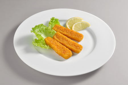 Round dish with fillet fish sticks breaded and fried isolated on grey background Stock Photo