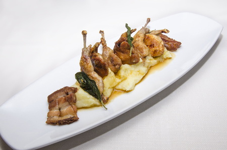 dish with portion of thighs of quail with bacon and mashed potatoes