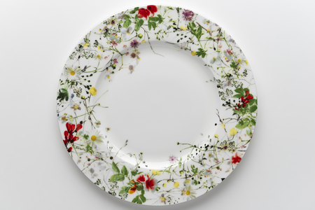Top view of Empty round dish decorated with painted flowers isolated on white background Imagens