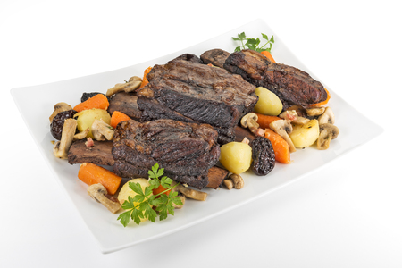 White rectangular plate with three cooked beef ribs mushrooms carrots and potatoes isolated on white background