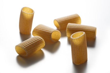 Selective focus on Some pieces of macaroni wholemeal pasta isolated on white background