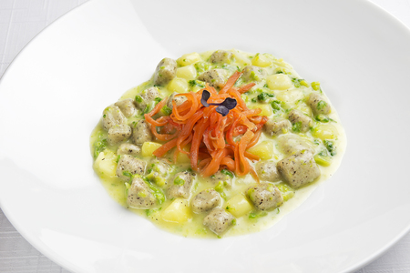 Plate with Buckwheat dumplings with cream of potato broccoli and salmonid trout Stock Photo