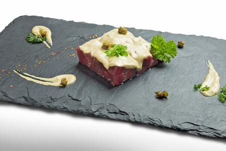 Bluefin tuna tartare with sauce on black slate Stock Photo