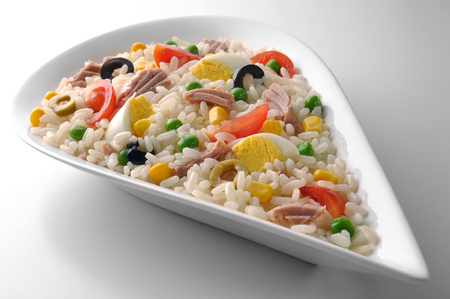 White drop-shaped bowl with rice eggs tuna and vegetables salad