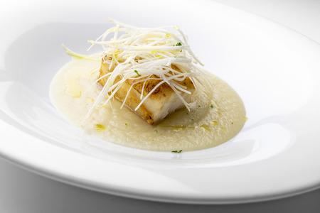 Isolated Fish dish, roasted cod with Verona celery puree