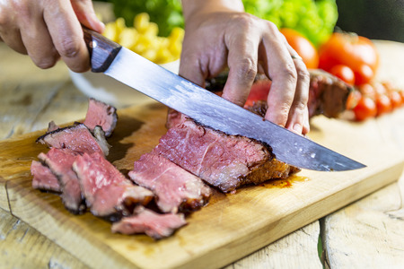Cutting of grilled beef steak on chopping board