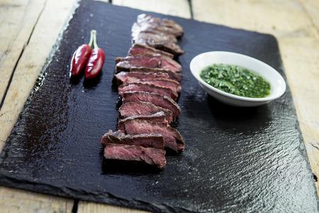 Slate plate with skirt steak pepper and chimichurri sauce