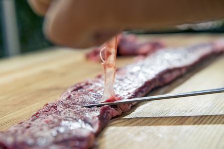 Butcher finishes Raw Skirt Steak for the barbecue Foto de archivo