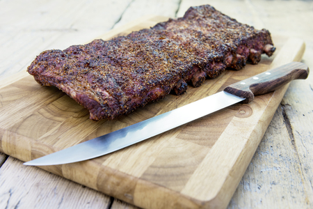 St Louis style grilled rack of pork ribs on cutting board