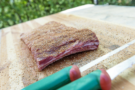Cutting board with Rack of Pork ribs seasoned ready for the grill Stock fotó