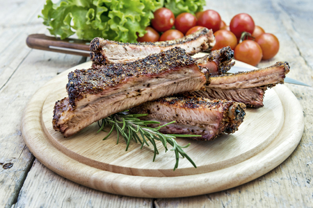 Round chopping board with grilled pork ribs tomatoes and salad