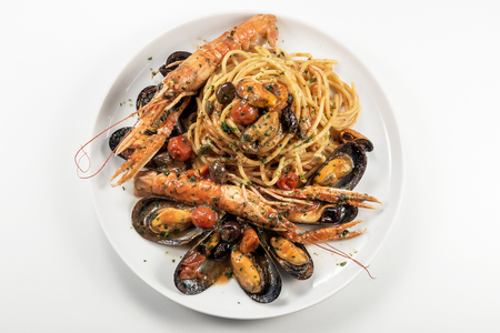Top view of Plate of spaghetti with prawn mussels olives and tomatoes