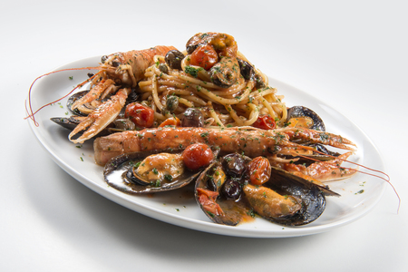 Plate of spaghetti with prawn mussels olives and tomatoes on white background