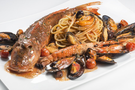 Rectangular plate of spaghetti with Tub gurnard fish prawn mussels olives and tomatoes