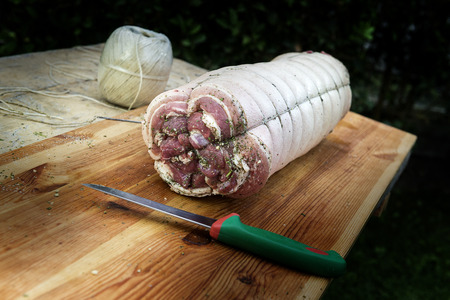 Chopping board with porchetta roast pork ready to cook