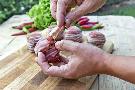 Preparation of meatballs stuffed with cheese and covered with bacon
