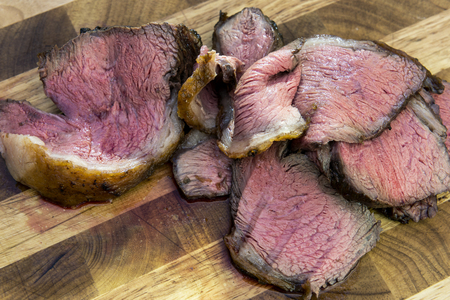 Slices of cooked meat picanha on chopping board