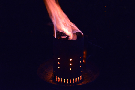 Activated charcoal with flames in a chimney for barbecue in the dark