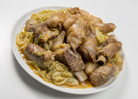 Plate with pork meat and savoy cabbage on white
