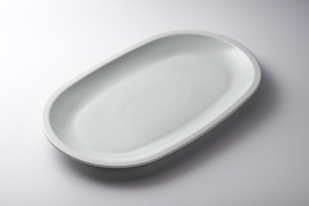 Isolated empty white oval plate on white background