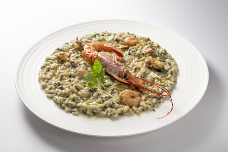 Risotto dish with prawns and seafood and parsley isolated