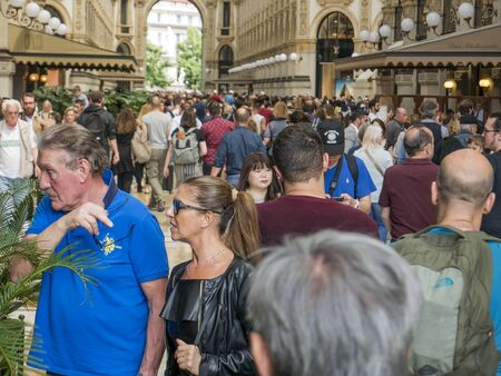 Milan, Italy - May 25, 2019: Crowd of tourists strolls for Saturday shopping in the Galleria Vittorio Emanuele in Milan
