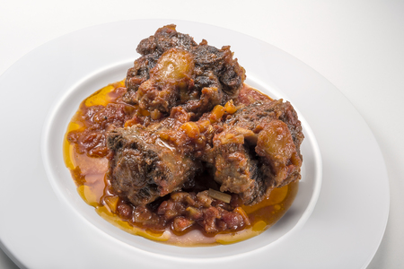 Dish with portion of oxtail stewed vaccinara isolated on white background