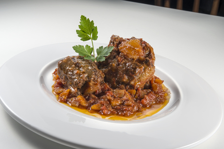 Dish with portion of oxtail stewed vaccinara with parsley Foto de archivo - 124480006