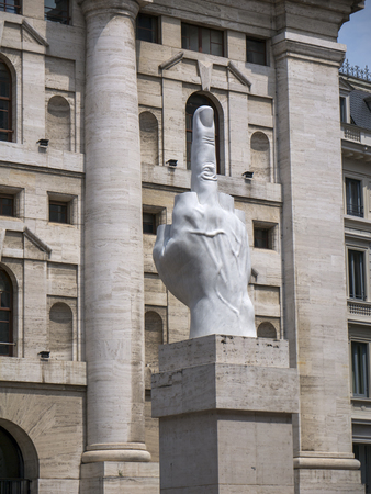 Milan, Italy - May 25, 2019: Middle finger sculpture and Mezzanotte Palace facade in Milan Stock Exchange, symbol and heart of Italian finance