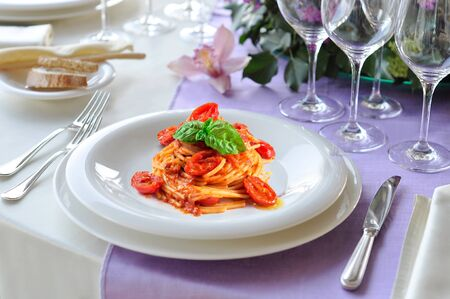 Table set with a plate of spaghetti tomato and basil