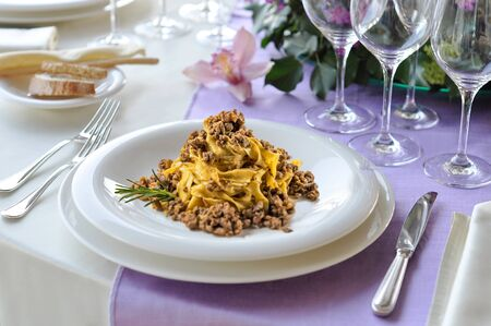 Table set with a plate of Bolognese tagliatelle