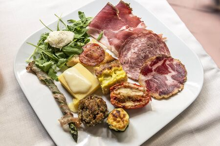 Plate with mixed Tuscan appetizer isolated on the table