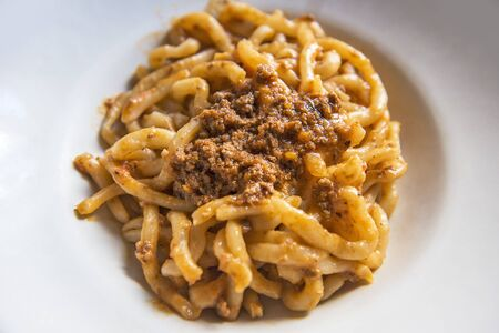 Tuscan pici pasta dish with meat sauce isolated on the table