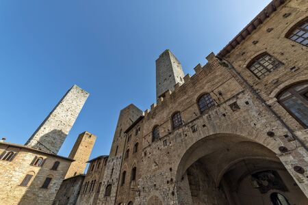 San Gimignano Siena Tuscany  Perspective view of Old palace of the podesta  rognosa tower and Chigi tower