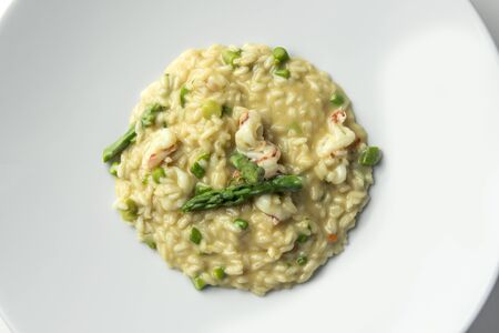 Top view of Plate of Risotto with green asparagus and prawns isolated on white
