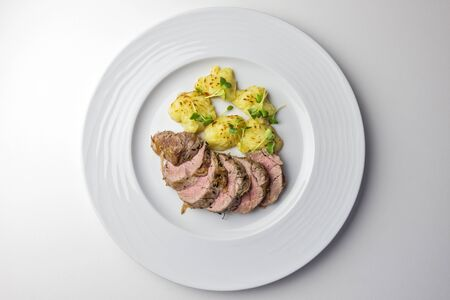 Plate with Pork fillet with gratinated potatoes isolated on white Banco de Imagens