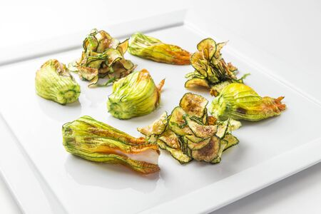 Plate of Stuffed Pumpkin Flowers with fish with courgette chips isolated on white Banco de Imagens