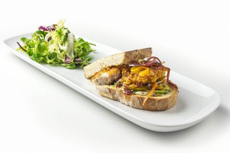 Plate with Breaded fish fillet sandwich with vegetables and mustard isolated on white