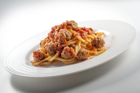 Plate of spaghetti with tomato and meatballs on white background Foto de archivo