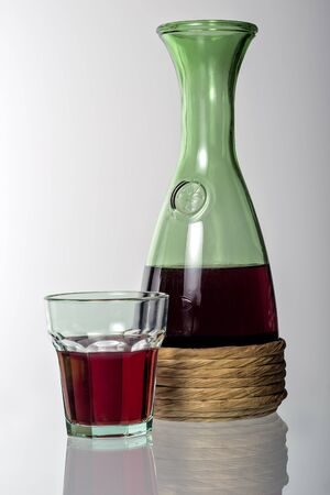 Typical tavern straw bottle and glass with red wine isolated on white