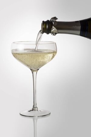 Bottle pouring sparkling wine into champagne cup glass isolated with clipping path 写真素材