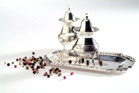 Salt and pepper set in silver plated with different peppercorns isolated on white