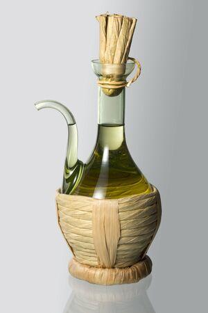 Glass oil cruet with straw on white 写真素材