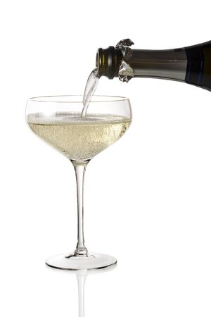 Bottle pouring sparkling wine into champagne cup glass isolated on white