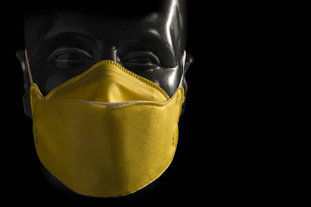 Anti-contagion protective yellow mask on transparent dummy head isolated on black background 写真素材