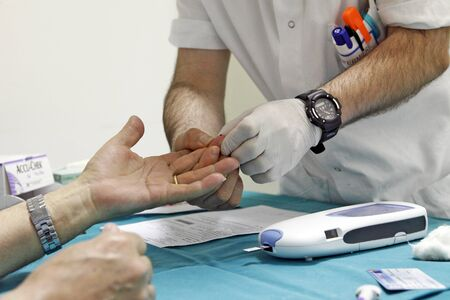 Milan, Italy - March 17, 2020: Blood sampling from the finger for blood glucose measurement 写真素材