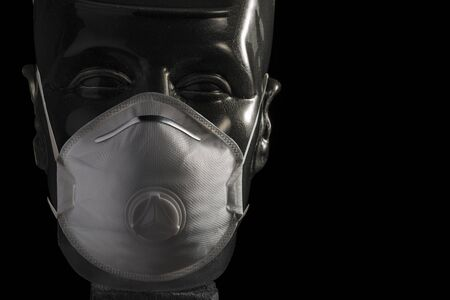 Anti-contagion protective white mask on transparent dummy head isolated on black background 写真素材