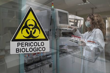 Milan, Italy - March 17, 2020: Biohazard symbol on glass window of Laboratory for biological analyzes 写真素材