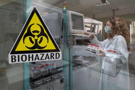Milan, Italy - March 17, 2020: Biohazard symbol on glass window of Laboratory for biological analyzes 報道画像