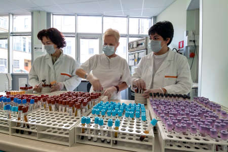 Milan, Italy - March 17, 2020: Operators Sorting of blood tubes in a rack in the analysis laboratory 報道画像